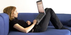 Woman sitting on couch with laptop computer.  She is browsing the internet wirelessly.
